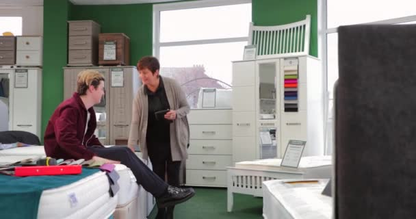 Mladý muž dostává Rady od prodavač v prodejně nábytku. On se snaží nové matrace