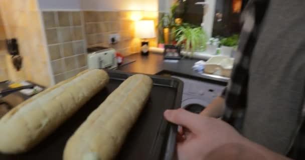 Jeden mladý muž je uvedení dvou česnekové bagety chleba v do trouby vařit