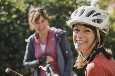 Headshot of a mature female wearing a cycling helmet and looking at the camera and smiling.