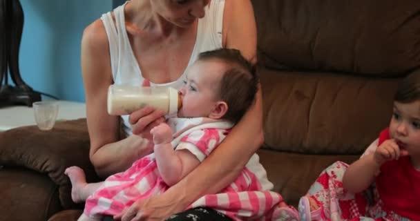 Matka, krmit jí holčička, zatímco její ostatní děti hrát