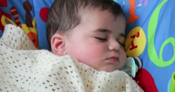 Malý chlapec spí v dětské lehátko, její figurína má padla z úst a leží vedle tváře