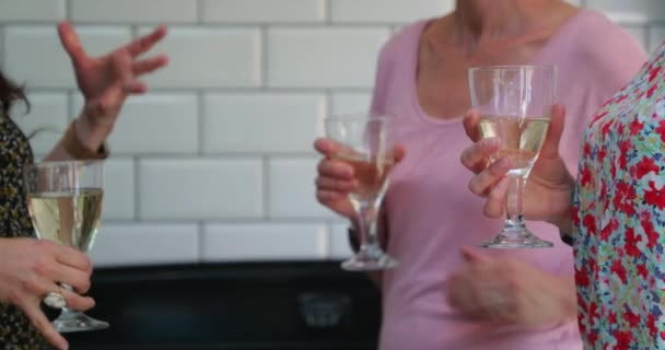Three mid-adult women having a glass of wine while catching up.