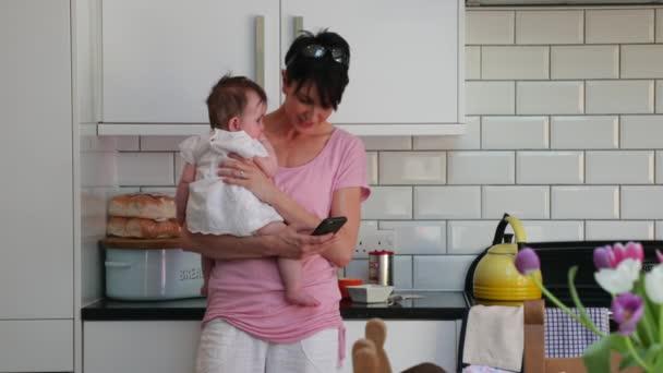 Matka drží svou dcerku, zatímco její další holčička je pobíhal kolem, u jejích nohou, ona se rovněž snaží volat ve stejné době