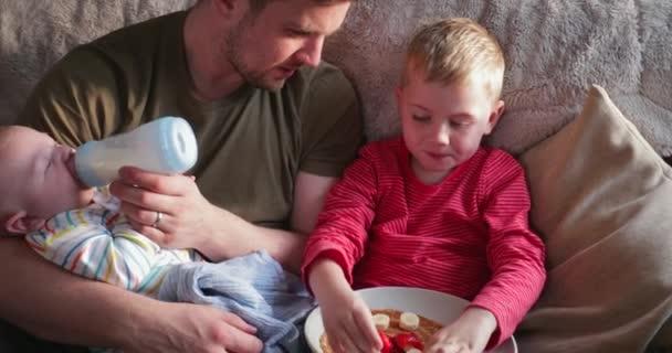 Malý chlapec jí lívance s banánů a jahod a zálivky, zatímco jeho malý bratr je láhev krmení jeho Tatínek