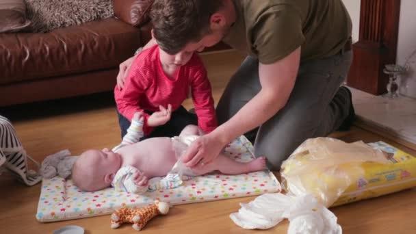 Malý chlapec pomáhal svému otci v obývacím pokoji se změnou jeho bratři plenky baby. Jeho otec mu upevnění pleny pomáhá