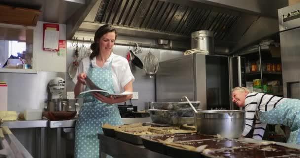 ein Koch hebt frische Kuchen aus dem Ofen, während der andere Koch in der Küche ein Kochbuch liest.