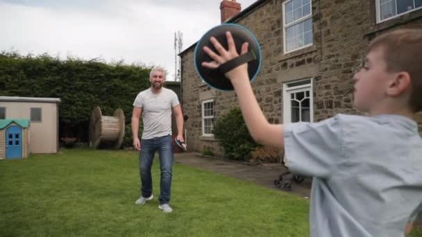 Malý chlapec a jeho otec stojí venku v zadní zahradě. Theya re se chytat s tenisový míček a Velcro palčáky