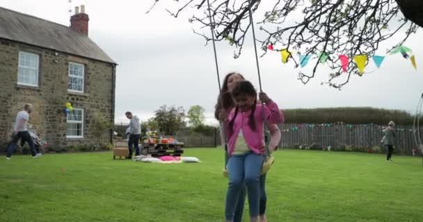 Malá holčička hrát venku na houpačce, zatímco ji její matka pomáhá a tlačí ji. Ona je baví a baví