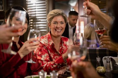 Cheerful mature woman raising her glass for a celebratory toast with her friends while sitting in a restaurant having a meal.