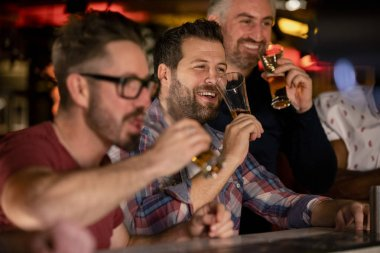 Three mid adult male friends enjoying a beer together in a bar.