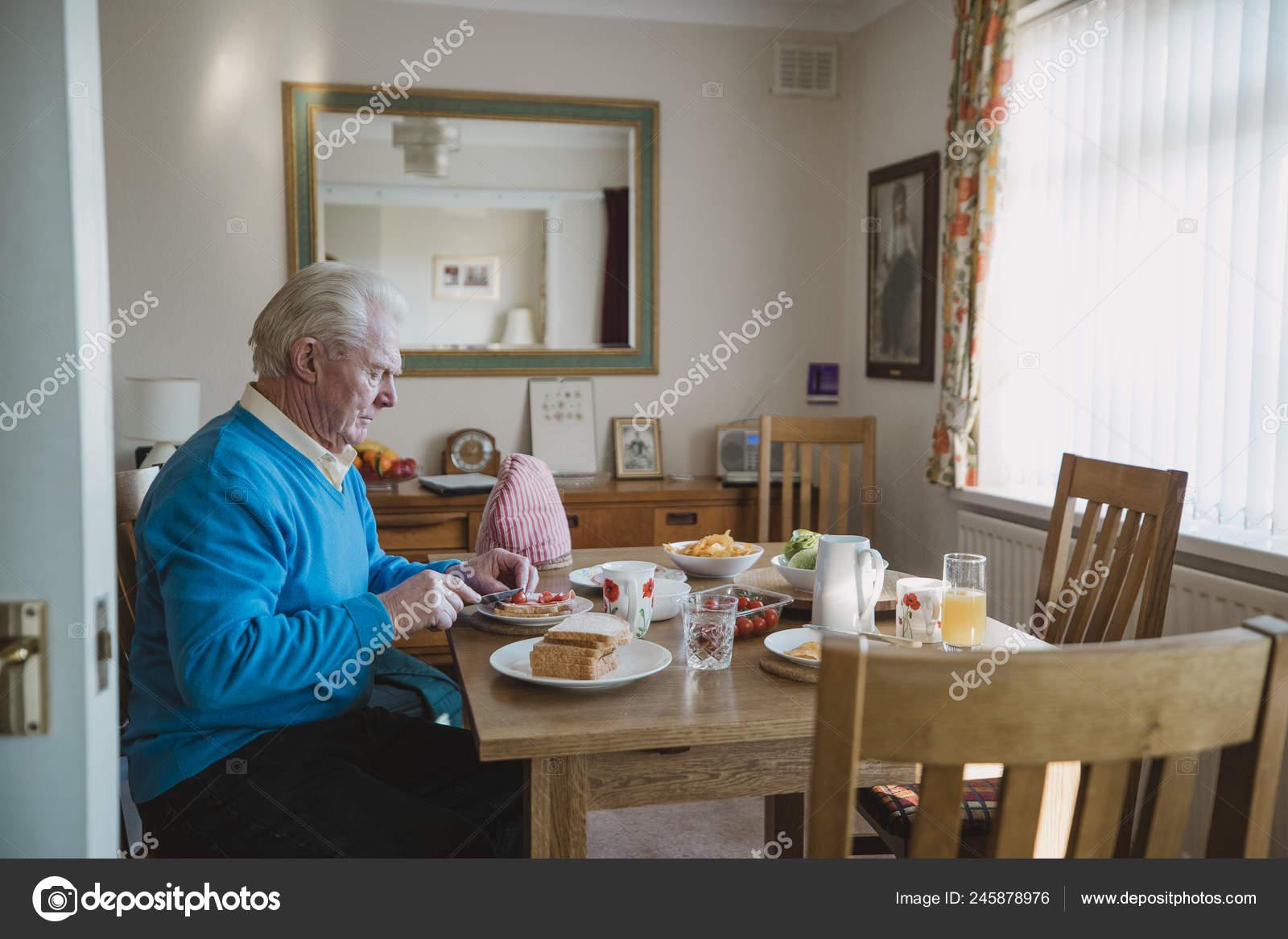 Hombre Mayor Está Sentado Mesa Comedor Casa Almorzando Está Haciendo ...