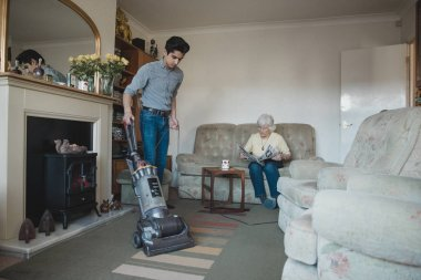 Teenage boy is hoovering his grandmother's living room for her while she reads a newspaper.