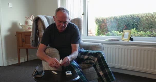 Starší diabetik muž kontroluje jeho hladiny cukru v krvi doma