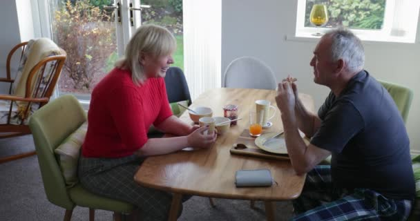 Mature woman and her senior partner are having breakfast together at home.