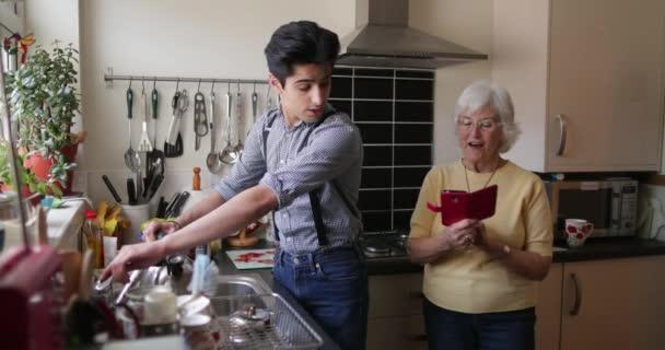 Seniorin zeigt ihrem Enkel etwas auf ihrem Smartphone, während er den Wasserkocher an der Spüle in ihrer Wohnung füllt. Sie lachen beide.