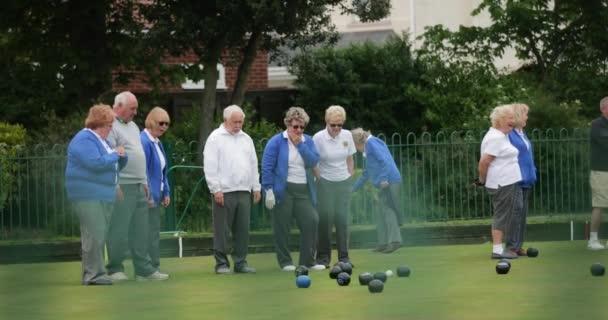 Boční panning záběr skupiny starších přátel trávníku bowling na trávě.