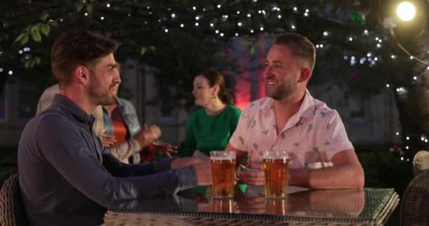 LGBTQI Couple sitting down and drinking champagne outdoors at a bar/restaurant, celebrating and having fun together.