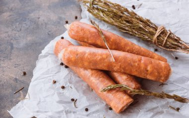 Raw sausages on a dark rustic metallic background. Meat sausages with spices on a baking paper