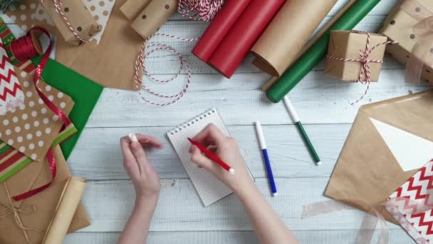 Ženské teen ruční psaní seznam dárků do Santa na dřevěný stůl s dárky, balicí papír, červená vánoční dekorace. Vánoce a šťastný nový rok složení. Plochá ležel, horní pohled