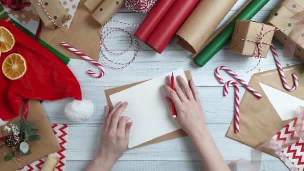 Ženské teen ruka psát dopis do Santa na dřevěný stůl s dárky, balicí papír, červená vánoční dekorace. Vánoce a šťastný nový rok složení. Plochá ležel, horní pohled