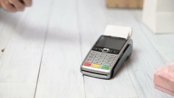A nő NFC technológiával fizet bankkártyán. Fizetés terminál fehér fa háttér. Ajándékdobozok és pont eladó terminál vagy POS nyugta. Hely másolása a szövegbe