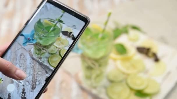 hogy egy fotót a Cool limonádé vagy Mojito koktél citrommal, lime, és a bazsalikom a telefon kamera. Hideg frissítő ital vagy jégital a fa rusztikus asztalán.