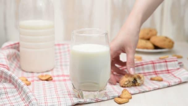 Ženská ruka Odplení koláčového chipu v mléce. Chutné sladké jídlo
