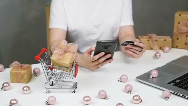 Karácsonyi online vásárlás. Egy nő kezében bankkártya. Fehér asztal ajándékdobozokkal és kis bevásárlókocsival. December 25-én a fa naptárban. Lapos fekvésű, felülnézet.