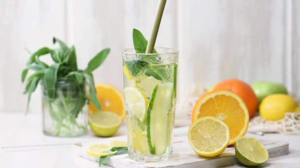 Citrus lemonade in a glass with drops and ice cubes. Fruit water, summer beverage on a wooden table