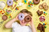 Fotografie Junge mit einer Auswahl an Süßigkeiten auf hellem Hintergrund