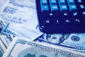 Pozadí s americkým dolarem, šekem a černou kalkulačkou. Hotovost.