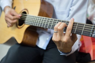 man practicing in playing guitar indoors