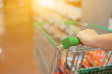 customer hand on shopping cart in supermarket