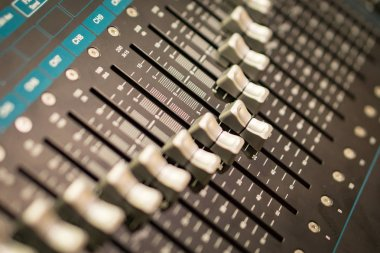 closeup on sliders of mixing console