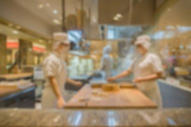 Blurred background with group of chefs cooking in restaurant kitchen