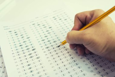 student finding right answers on test sheet with pencil