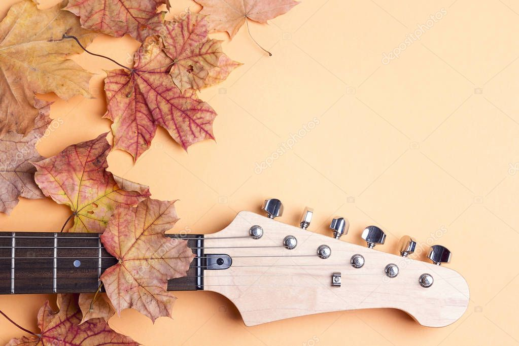 Electric guitar neck  with autumn maple leaves and copy space on yellow background. Melancholy music for autumn mood.
