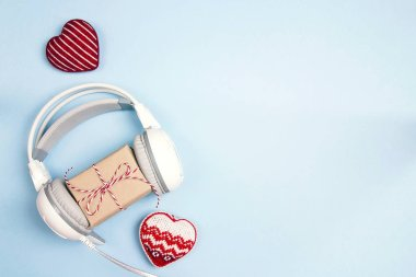 White headphones with gift box and decorative hearts on a blue background. Top view with copy space. Christmas music gift concept.