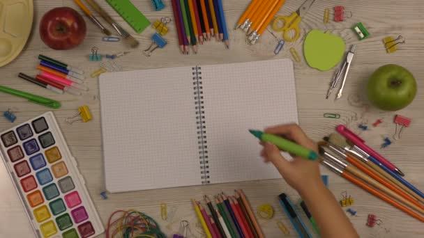 Lány leír-ban egy jegyzetfüzet hát-hoz iskola. Vissza az iskolába háttér iskolai ellátás az asztalra. Felülnézet lövés.