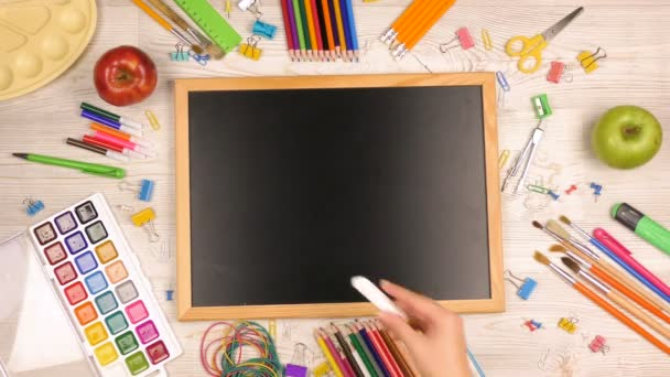 Back to school sale background with school supplies on the table. Girl writes in chalk on a blackboard word sale. Top view shooting.