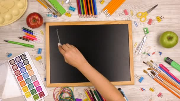 Girl writes in chalk on a blackboard back to school. Back to school background with school supplies on the table. Top view shooting.
