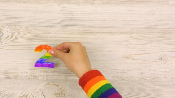 Female hand puts on the table rainbow colored figures 2020 on wooden background. LGBT Pride Month in June.