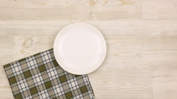 Apák napi asztal beállítása evőeszközökkel, sapkával és bajusszal a könnyű fa asztalon. Női kezek terítik meg az asztalt az ünnepre. Felülnézet.