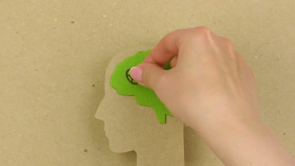 Silhouette human head with green brain and gears. Female hands put gears into the brain. Strategic thinking and planning concept.