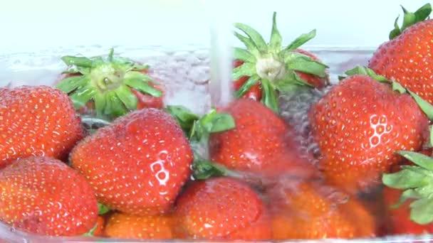 Mytí čerstvě zralé lahodné jahody pod tekoucí vodou. Jahody ve vodě s bublinkami. Šťavnaté ovoce by mělo být důkladně umyté a snědené.