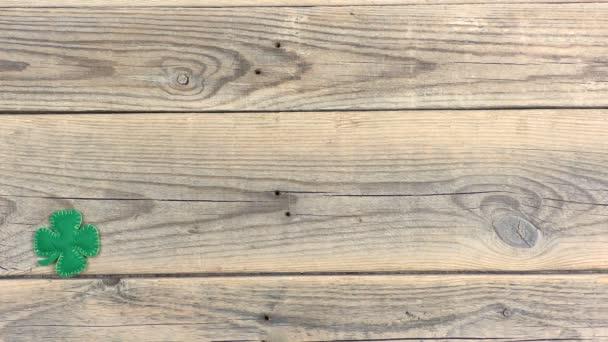 Samičí ruka leží na starém dřevěném pozadí ohraničená plstěným čtyřlístkovým jetelem. Lucky Shamrock, symbol svátků svatého Patrika. Mezera pro text, pohled shora.
