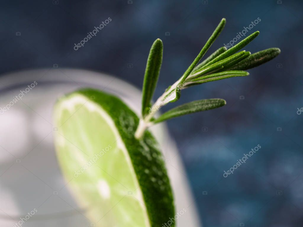Glass of alcoholic coctail with fresh rosemary and lime on blue background. Close up. Shallow DOF