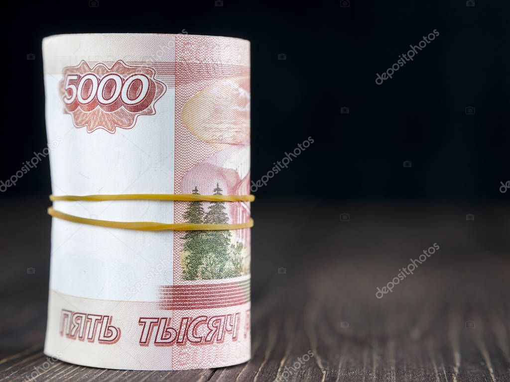 roll of five thousandth rubles notes on wooden background