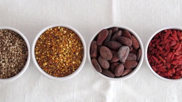 Superfood und Detox-Zutaten in kleiner Schüssel auf weißem Leinentischtuch. verschiedene Superfoods wie Matcha-Tee, Chia-Samen, Goji, Spirulina, Kakaobohne. natürliches Tageslicht.Nahaufsicht.Ansicht von oben oder von oben
