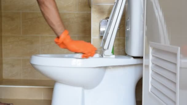 Egy ember visel narancssárga gumi kesztyűt kezét hozzászokott megtérít, Polírozó, hogy a WC.